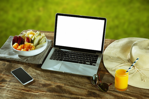 Blank screens of laptop and smartphone on a wooden table outdoors with nature on wall fruits and fresh juice nearby. concept of creative workplace, business, freelance. copyspace. Free Photo