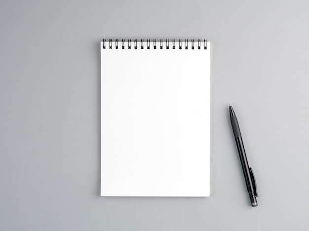 Blank sheet of notebook  a spiral and pen on a neutral gray textured  background Premium Photo