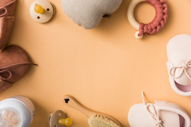Blank space for text with pair of shoes; pacifier; stuffed pear; brush; milk bottle on an orange backdrop Free Photo