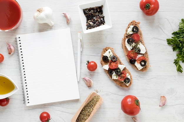 Blank spiral diary and bruschetta with ingredient on wooden table Free Photo