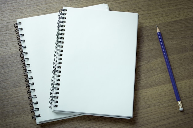 Blank spiral notebook and pencil on dark wood background Free Photo