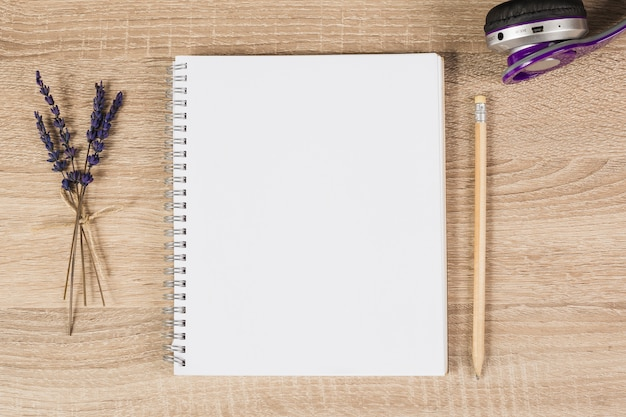 Blank spiral notebook; pencil; headphone and lavender twigs on wooden background Free Photo