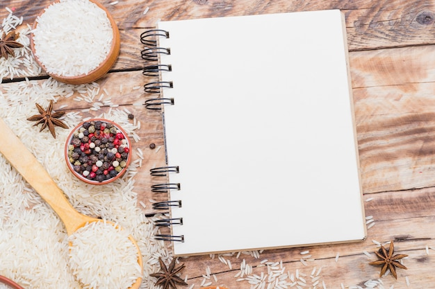 Blank spiral notebook; raw rice and dry spices on wooden wallpaper Free Photo