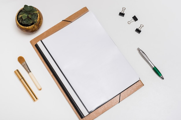 Blank spiral notebook with make-up brush; mascara; paper clips and pen with potted plant on white desk Free Photo