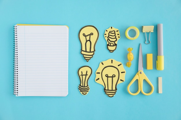 Blank spiral notebook with paper light bulbs and stationery on blue background Free Photo