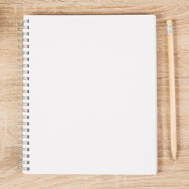 Blank spiral notebook and wooden pencil on wooden desk Free Photo