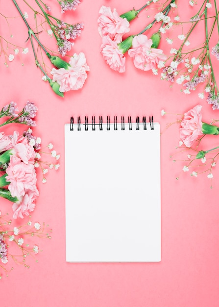 Blank spiral notepad decorated with carnations; gypsophila; limonium flowers on pink background Free Photo