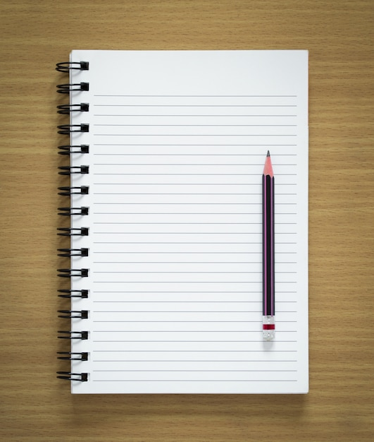 Blank spiral notepad and pencil on wood background Free Photo