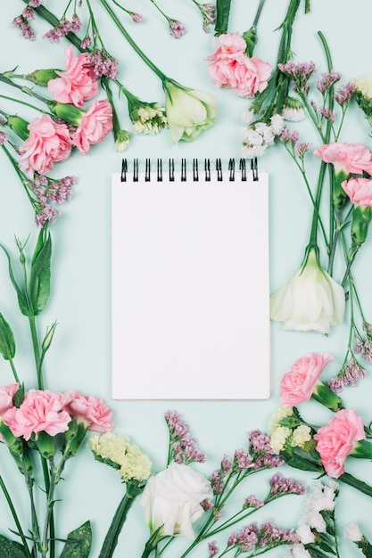 Blank spiral notepad surrounded with limonium; carnations and eustoma flowers against blue background Free Photo
