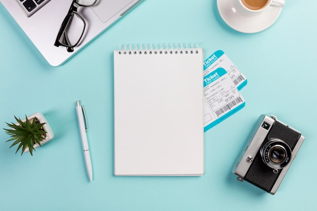 Blank spiral notepad with air tickets surrounded with laptop,eyeglasses,pen,camera,coffee cup on blue desk Free Photo