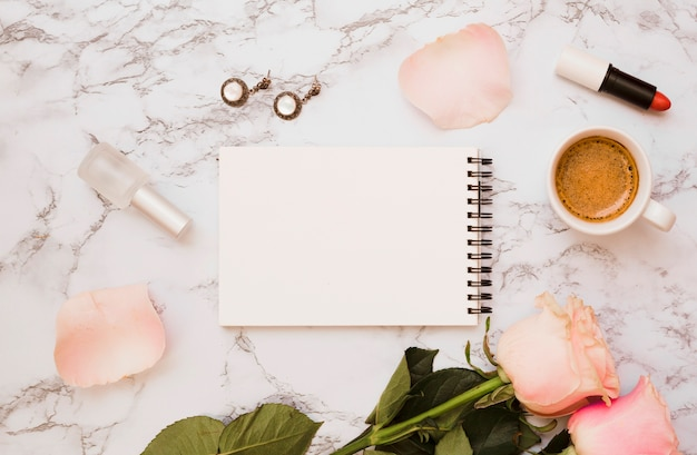 Blank spiral notepad with earrings; nail varnish bottle; lipstick; roses and coffee cup on marble background Free Photo