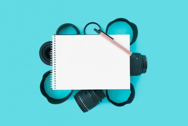 Blank spiral notepad with pen over camera accessories on blue background Free Photo