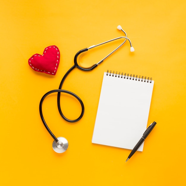 Blank spiral notepad with pen; stitched heart shape; stethoscope above bright yellow backdrop Free Photo