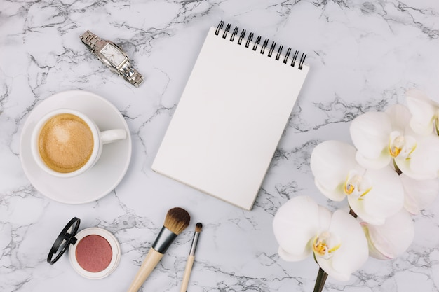 Blank spiral notepad; wristwatch; coffee cup; compact powder; makeup brush and white orchid flower on marble textured background Free Photo
