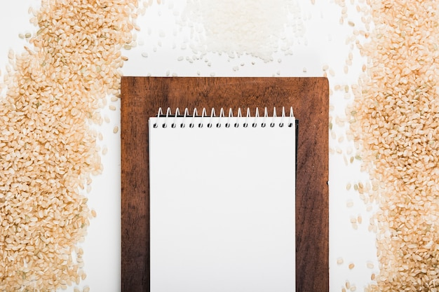 Blank spiral white notepad over the brown wooden board with uncooked rice on white background Free Photo