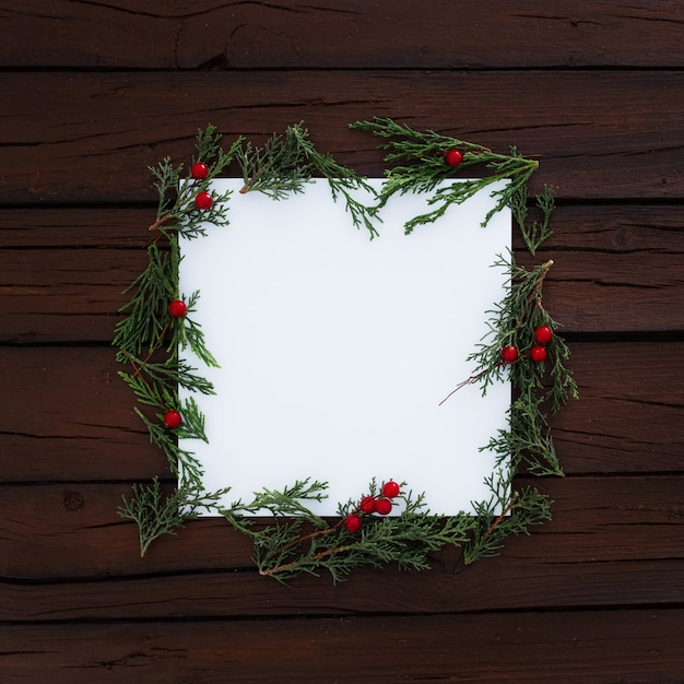 Blank square with christmas pine leaves around on rustic wooden background Free Photo