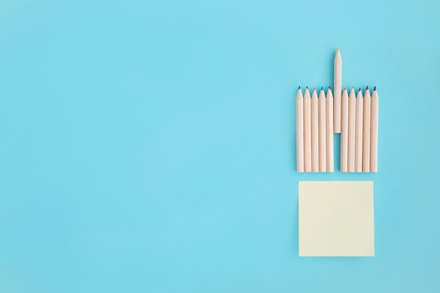 Blank sticky note with rows of colored pencil over blue background Free Photo