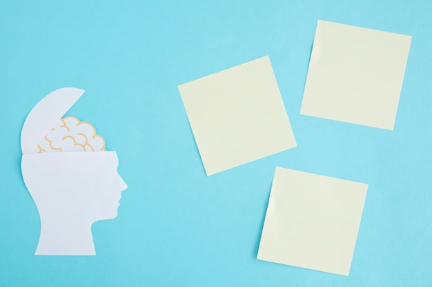 Blank sticky notes with brain in the open head on blue background Free Photo