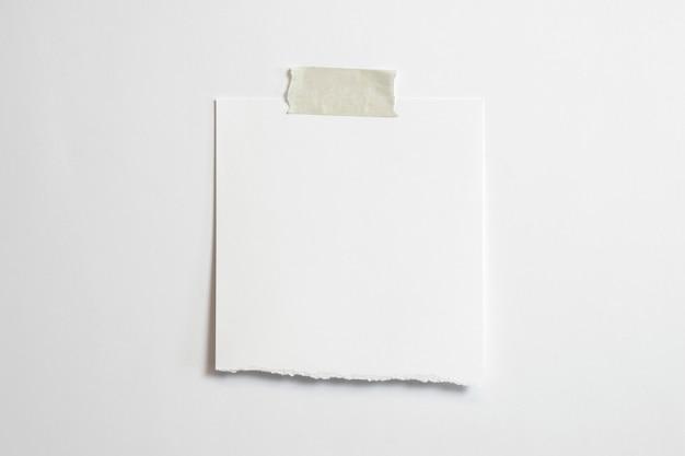 ソフトシャドウとホワイトペーパーの背景に分離されたスコッチテープの空白の破れたフォトフレーム 無料写真