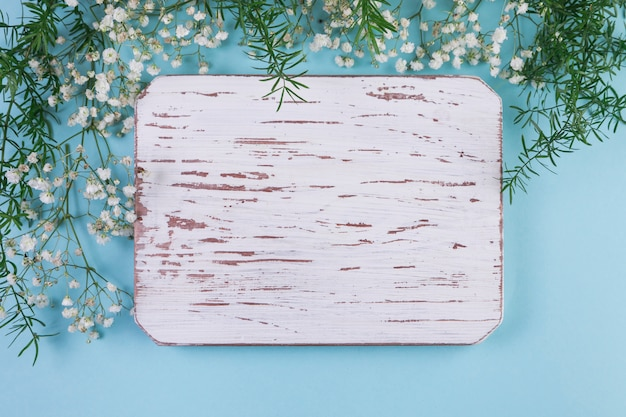 Blank weathered white wooden frame with baby's breath flowers and leaves against blue background Free Photo