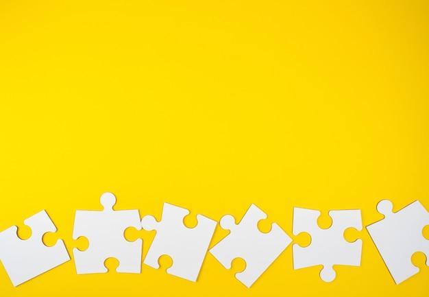 Blank white big puzzles on yellow background, flat lay Premium Photo