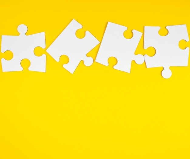 Blank white big puzzles on yellow background Premium Photo