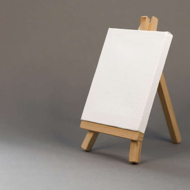 Blank white canvas on easel on gray background Premium Photo