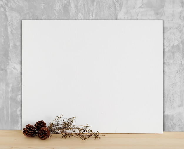 Blank white canvas frame on wood floor and cement wall background ...