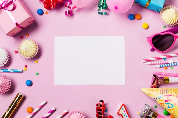 Blank white card surrounded with birthday items on pink background Free Photo