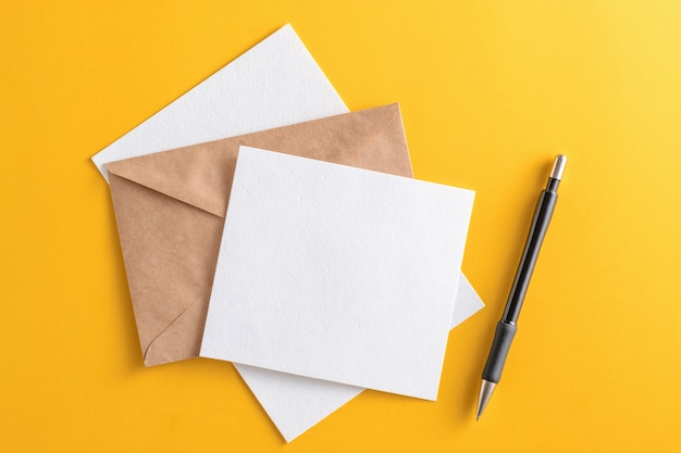 Blank white card with kraft brown paper envelope and pencil on yellow background Premium Photo