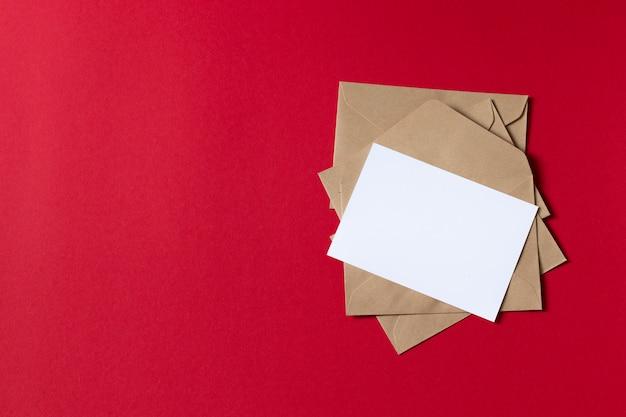 크래프트 갈색 종이 봉투 템플릿 빈 흰색 카드는 빨간색 배경에 조롱 프리미엄 사진