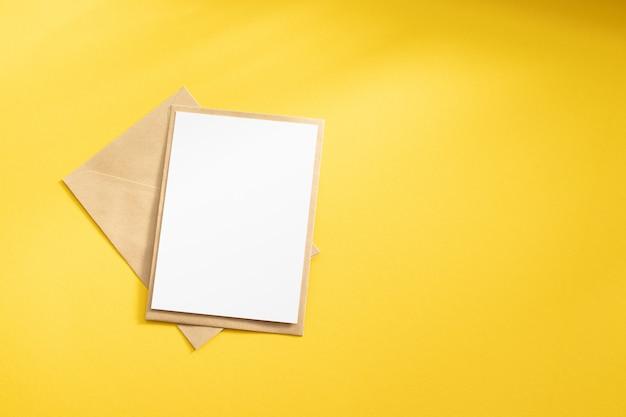 크래프트 갈색 종이 봉투 템플릿 빈 흰색 카드는 노란색 배경에 조롱 프리미엄 사진