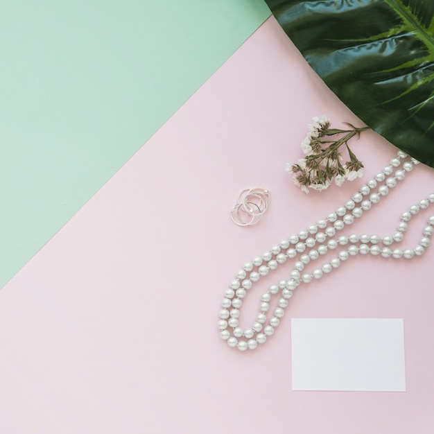 Blank white card with pearls necklace, flower and leaf on backdrop Free Photo