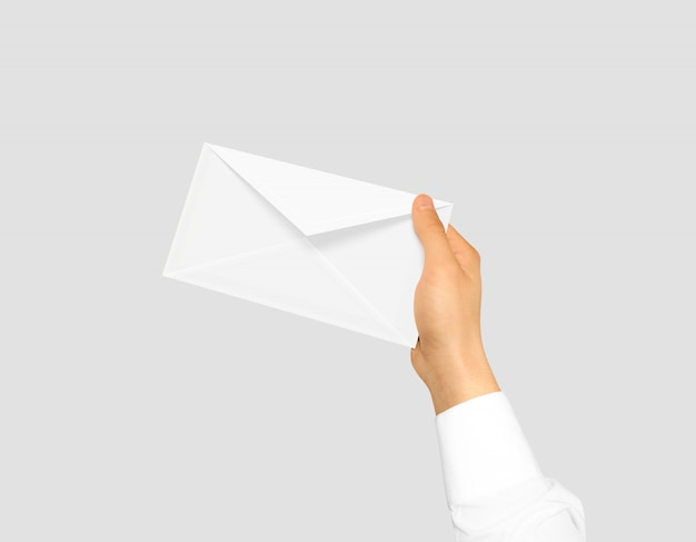Blank white envelope mock up holding in hand. Premium Photo