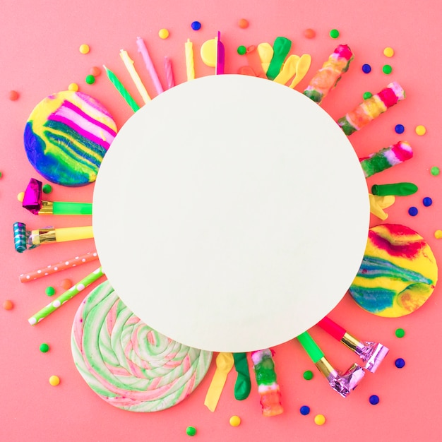 Blank white frame over party accessories and candies on pink surface Free Photo