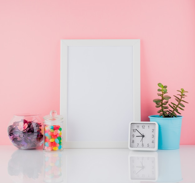 Blank white frame and plant cactus,  sweet candy in jar on white Premium Photo