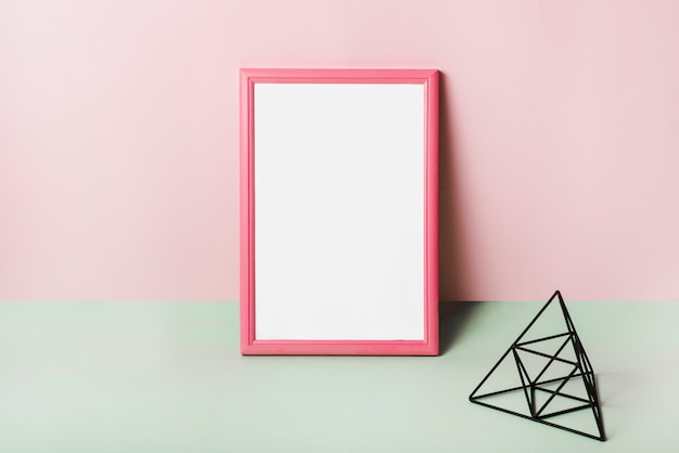 Blank white frame with pink border against pink background Free Photo