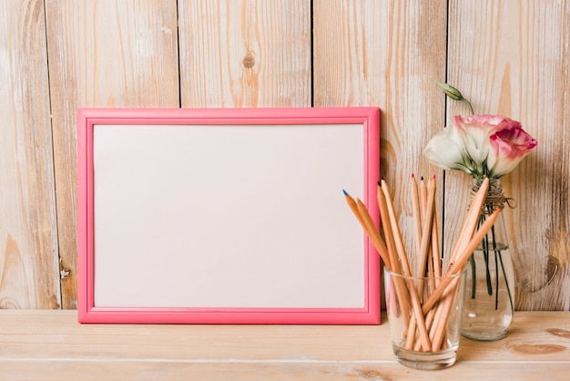 Blank white frame with pink border and colored pencils in glass on wooden desk Free Photo