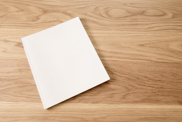 Blank white magazine cover on wooden table background. Premium Photo