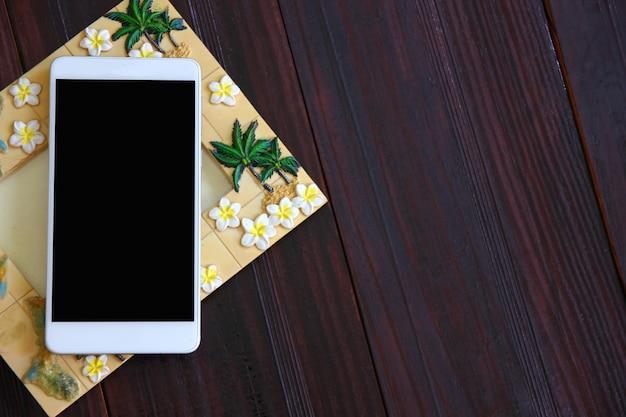 갈색 나무 바닥에 액자와 빈 흰색 휴대 전화 프리미엄 사진