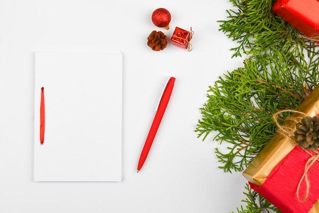 空白の白いノートと白いクリスマススペースに赤ペン。クリスマスのモミの枝、コーン、ギフト。サンタクロースへの手紙、モックアップ。空白の白いノートと白に赤ペン。 Premium写真