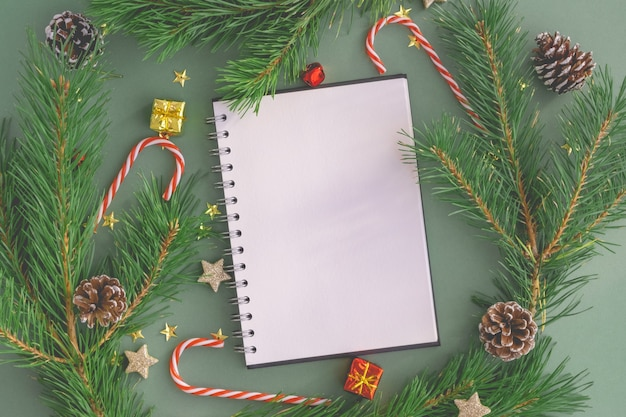 Blank white open notebook with a pen on a christmas background made of trees, toys and christmas candies Premium Photo
