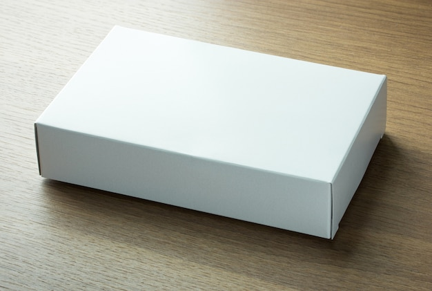 Blank white paper box on dark wood background Free Photo