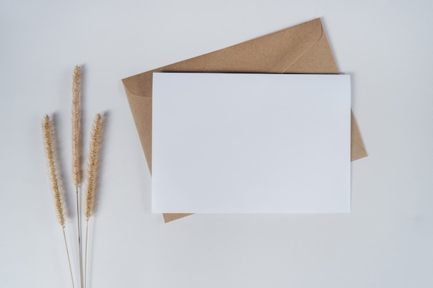 Blank white paper on brown paper envelope with bristly foxtail dry flower. top view of craft paper envelope on white background. Premium Photo