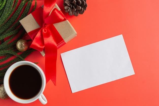 Un libro bianco vuoto, una tazza di caffè e una confezione regalo sul pavimento rosso Foto Gratuite