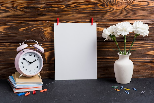 Blank white paper; vase; alarm clock and notebooks against wooden backdrop Free Photo