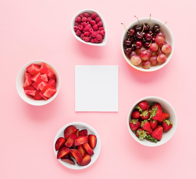 Blank white paper with bowls of red color fruits on pink background Free Photo