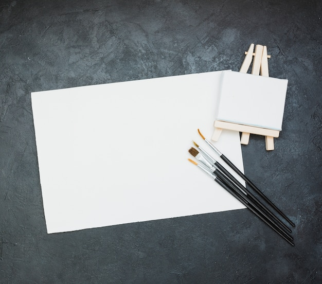 Blank white paper with mini easel and paintbrush on slate backdrop Free Photo