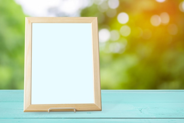 Blank white picture frame on the wall and the table wood Premium Photo