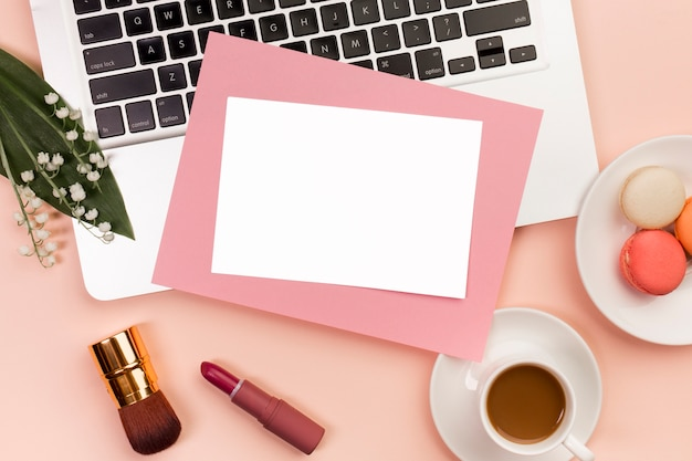 Blank white and pink paper on laptop with lipstick,makeup brush and coffee cup with macaroons over the office desk Free Photo